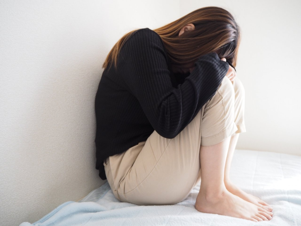 經痛吃什麼配圖:女生蜷縮在床上